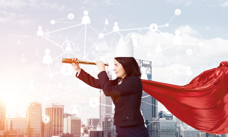 Young confident businesswoman wearing red cape against modern city background and looking in spyglass Imagens