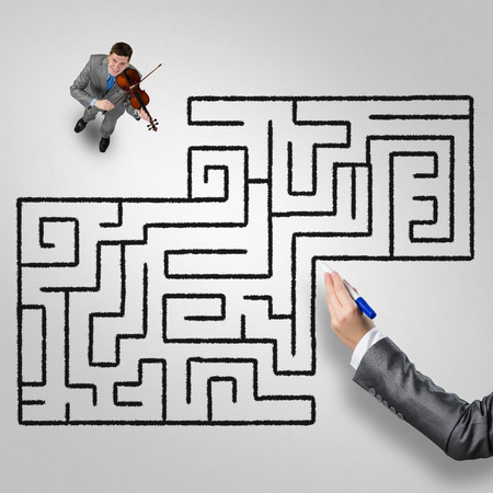 Top view of businessman playing violin and drawn labyrinth on floor Stock Photo