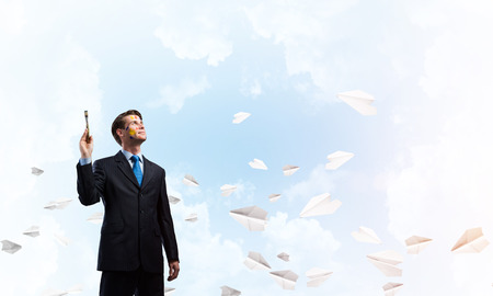 Portrait of ambitious and young business man in suit holding paintbrush in hand while standing against blue cloudy skyscape view with flying paper planes on background. Imagens