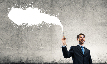 Portrait of young and successful businessman in black suit holding paintbrush in hand while standing with white musical liquid splash and against gray dark background Archivio Fotografico - 119335430
