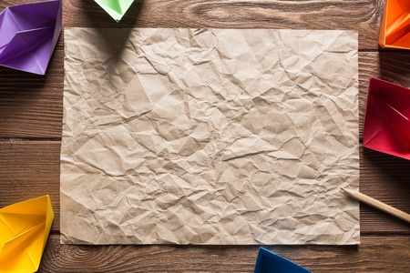 Crumpled brown paper sheet and pencil on wooden table Stock Photo - 119438709