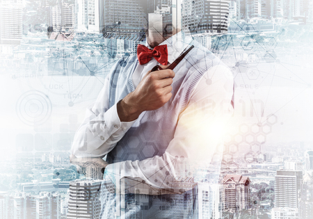 Confident and young businessman in smart-casual wear smoking pipe and modern cityscape with business and media interface. Double exposure Concept of new technologies for modern business. Imagens