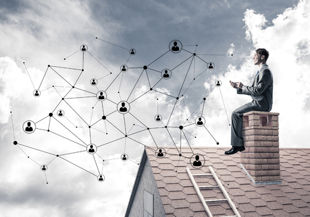 Young businessman sitting on house chimney with smartphone in hands