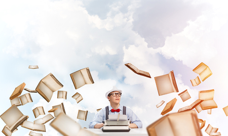 Young man writer in hat and eyeglasses using typing machine while sitting at the table among flying books with cloudy skyscape on background.