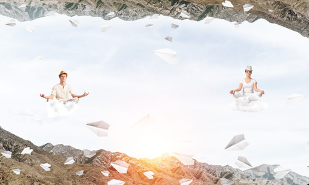 Young couple keeping eyes closed and looking concentrated while meditating on clouds among flying paper planes and between two nature worlds.