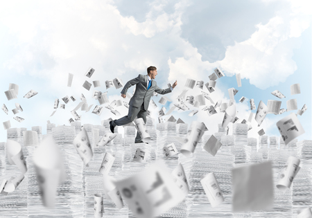 Businessman in black suit running with phone in hand among flying papers with cloudly skyscape on background. Mixed media. Imagens