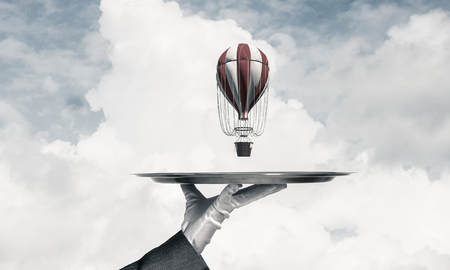 Closeup of waiters hand in glove presenting flying aerostat on metal tray with blue cloudy skyscape on background. 3D rendering.