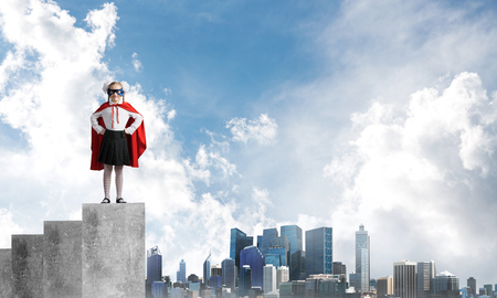 Young girl in superhero costume standing on concrete graph. Mixed media Reklamní fotografie