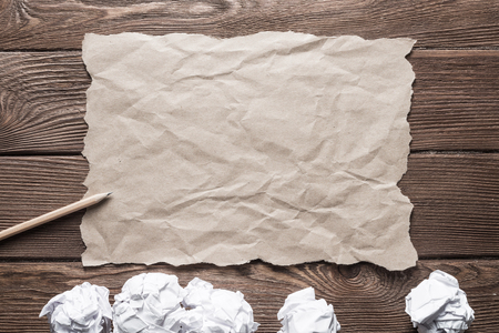 Crumpled brown paper sheet and pencil on wooden table Stock Photo - 119484849