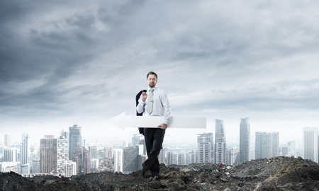Horizontal shot of young businessman holding white arrow which is pointing sideways while standing against cityscape view and cloudy sky on background. 版權商用圖片