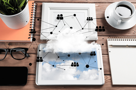 Top view of modern workplace with office stuff, social network connections and clouds above as symbol of still office life. Mixed media. Banco de Imagens