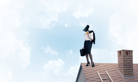 Faceless businesswoman with camera zoom instead of head standing on house roof Foto de archivo