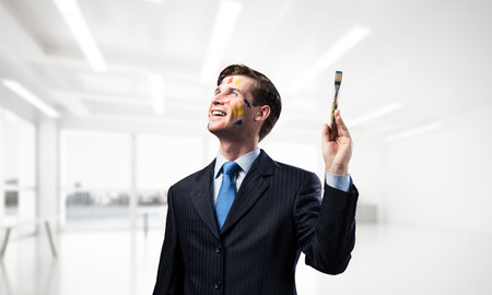 Studio shot of successful and confident businessman keeping paintbrush in his hand and looking away while standing inside bright office building.