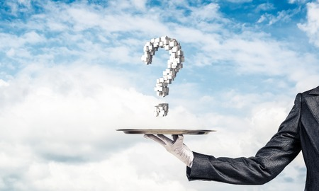 Cropped image of waitresss hand in white glove presenting multiple cubes in form of question mark on metal tray with cloudy skyscape on background.