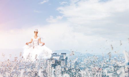 Woman in white clothing keeping eyes closed and looking concentrated while meditating on cloud among flying letters with cityscape view on background. 版權商用圖片