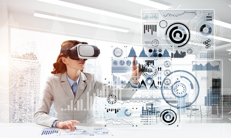Portrait of confident and successful business woman in suit sitting inside office building with digital media interface and using virtual reality headset Stock Photo - 119649144