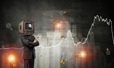 Businessman in suit with old TV instead of head keeping arms crossed while standing against flying bulbs and analytical charts drawn on wall on background. 3D rendering. Stock Photo