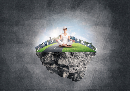 Woman in white clothing keeping eyes closed and looking concentrated while meditating on flying island in the air with gray dark wall on background. 3D rendering.