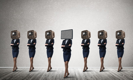 Businessmen in suits with old TV instead of their heads keeping arms crossed while standing in a row and one at the head with TV in empty room against gray wall on background. Stock Photo