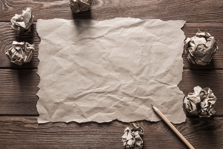 Crumpled brown paper sheet and pencil on wooden table Stock Photo - 119682062