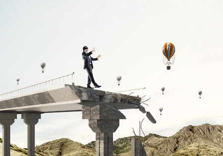 Businessman walking blindfolded on concrete bridge with huge gap as symbol of hidden threats and risks. Flying balloons and nature view on background. 3D rendering. Imagens