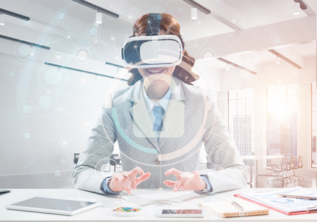 Confident and successful business woman in suit sitting inside office building with security interface and using virtual reality headset