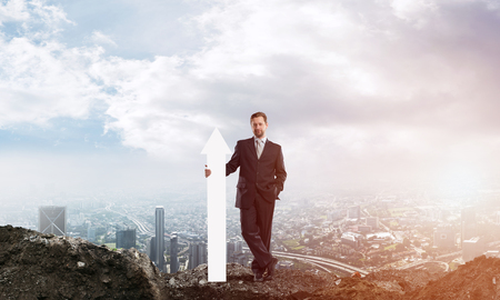 Conceptual image of young businessman keeping big white arrow in hands while standing against cityscape view and cloudy sky on background. 스톡 콘텐츠