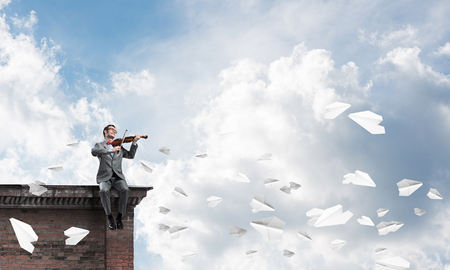 Young man wearing suit and glasses sitting on roof and playing violin Foto de archivo