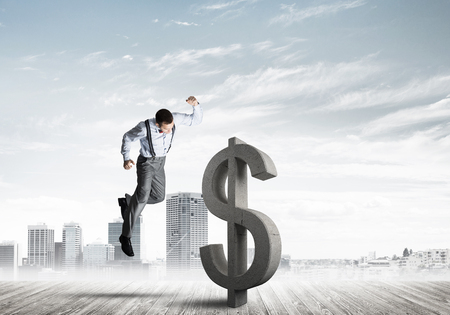 Young furious businessman going to crash with fist stone dollar symbol Banco de Imagens