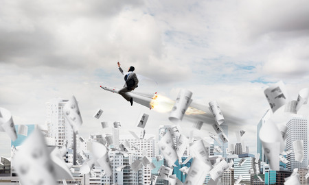 Conceptual image of young and happy businessman in suit flying on rocket among flying papers with modern cityscape with skyscrapers and blue sky on background. 免版税图像
