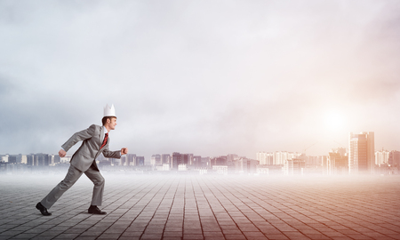 Young handsome businessman wearing white paper crown running in a hurry Фото со стока