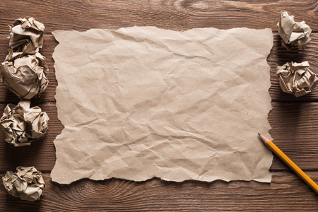 Crumpled brown paper sheet and pencil on wooden table Stock Photo - 119901018