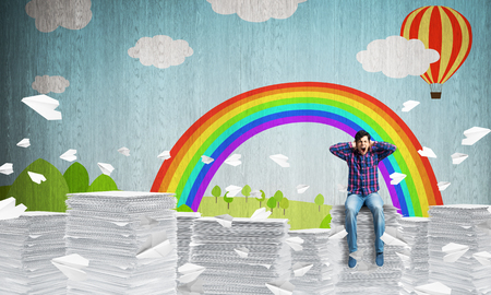 Attractive man in casual clothing sitting among flying paper planes with sketched landscape view on background. Mixed media. Imagens
