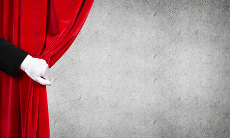 Close up of hand in white glove open red velvet curtain Imagens