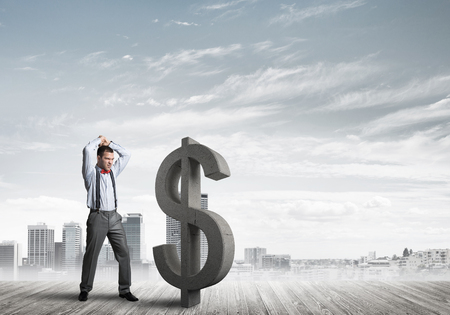 Young furious businessman going to crash with hands stone dollar symbol Imagens