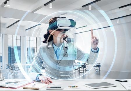 Horizontale Aufnahme der schönen und jungen Geschäftsfrau im Anzug unter Verwendung des Virtual-Reality-Headsets mit digitaler Sicherheitsschnittstelle beim Stehen im Büro. Standard-Bild
