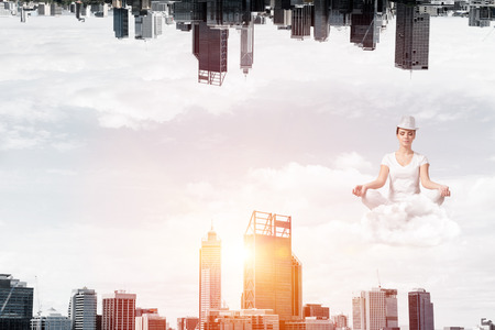 Young woman keeping eyes closed and looking concentrated while meditating on cloud in the air between two urban worlds.