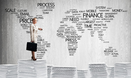 Business woman in suit standing on pile of documents with business-related terms in form of world map on background. Mixed media.
