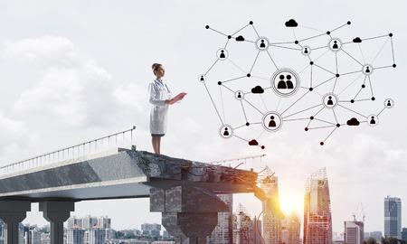 Jonge vrouwelijke arts in een wit medisch pak dat de sociale netwerkstructuur bestudeert terwijl hij aan het einde van een gebroken brug staat. Stadsgezicht op de achtergrond