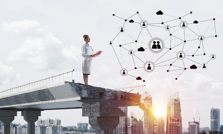 Young woman doctor in white medical suit studying social network structure while standing at the end of broken bridge. Cityscape view on background