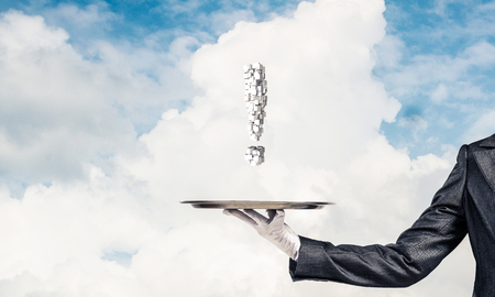 Cropped image of waitresss hand in white glove presenting multiple cubes in form of exclamation mark on metal tray with cloudy skyscape on background.