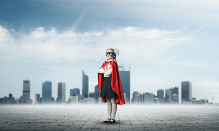 Little confident child in mask and cape plays cool superhero . Mixed media Imagens
