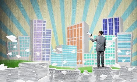 Businessman in suit standing among flying paper planes with speaker in hand with sketched cityscape view on background. Mixed media. Imagens