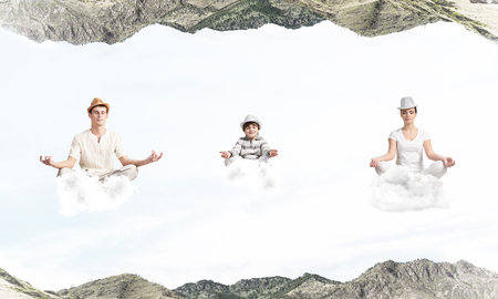 Young family keeping eyes closed and looking concentrated while meditating on clouds in the air between two nature worlds.