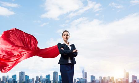 Joven empresaria segura vistiendo capa roja contra el fondo de la ciudad moderna