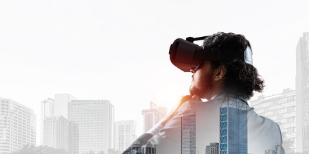 Double exposure of businessman in virtual helmet against cityscape background