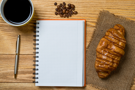 Opened notepad and cup of coffee with donut on wooden table Imagens