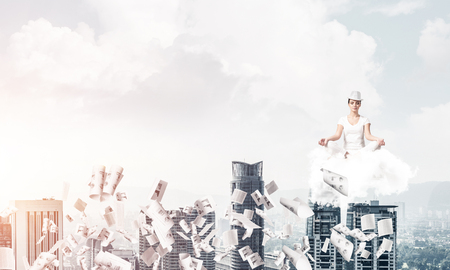 Woman in white clothing keeping eyes closed and looking concentrated while meditating on cloud among flying papers with cityscape view on background.