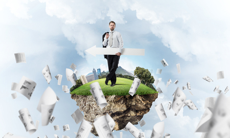 Confident young businessman in suit standing on flying island with huge white banner in hands which pointing away and with cloudy skyscape on background