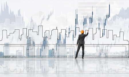 Young engineer in suit at balcony against morning cityscape background Stock Photo